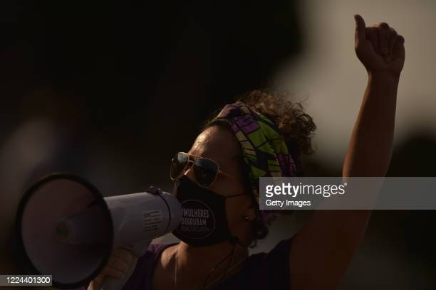 """Member of the 'Levante de Mulheres' group wearing a mask that reads """"Women bring down Bolsonaro"""" shouts on a megaphone during a rally against..."""