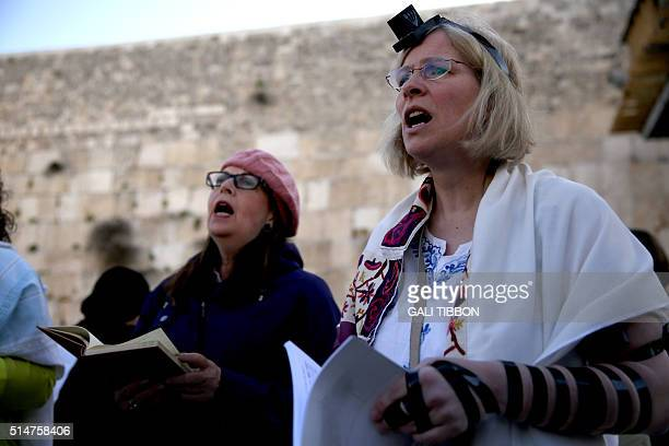 A member of the liberal Jewish religious group Women of the Wall wears phylacteries and Tallit traditional Jewish prayer shawls for men as she prays...