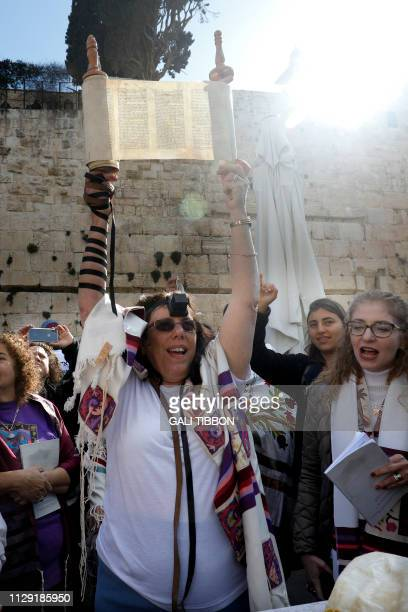 A member of the liberal Jewish religious movement Women of the Wall wearing phylacteries and Tallit traditional Jewish prayer shawls for men holds up...