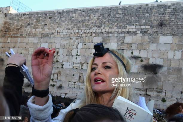 A member of the liberal Jewish religious movement Women of the Wall wearing Tefillin or phylacteries and Tallit prays during an event marking the...