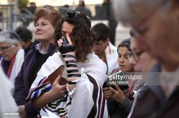 A member of the liberal religious group Women of the Wall wearing phylacteries and a Tallit traditional Jewish prayer shawl for men prays at the...