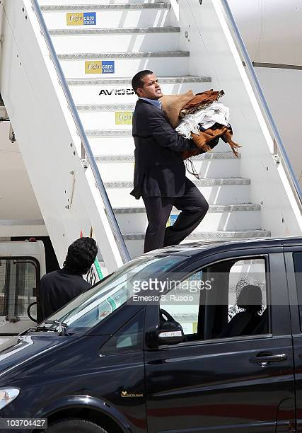A member of the Libyan leader Muammar Gaddafi's entourage carries clothes at Ciampino airport on August 29 2010 in Rome Italy Gadaffi is on an...