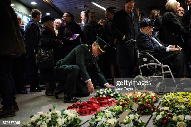 A member of the London Ambulance service lays a wreath during a memorial to mark the 30th anniversary of the King's Cross fire at King's Cross...