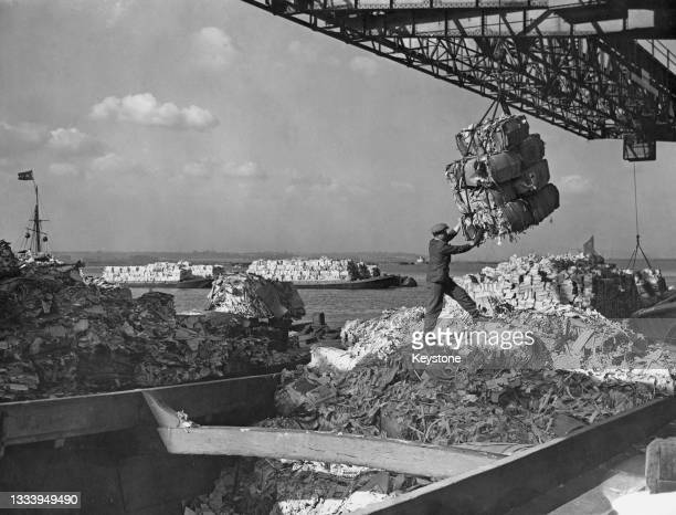 Member of the London Salvage Corps assists the loading of a barge with bundles of waste paper and cardboard as part of the drive to recycle paper and...