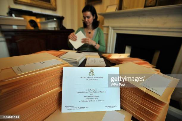 Member of the Lord Chamberlain's Office inserts Prince William and Kate Middleton's wedding invitations into envelopes at Buckingham Palace, on...