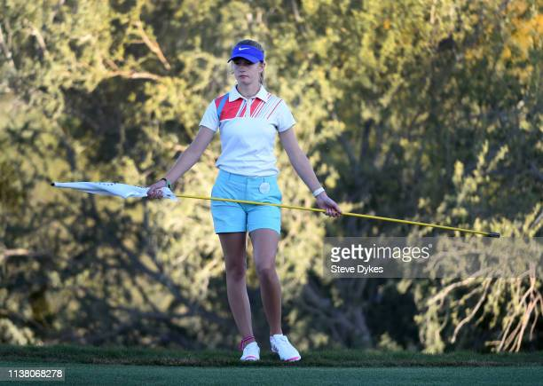 A member of the LPGAUSGA Girls Golf of Phoenix holds the flag stick on the 18th green during the final round of the Bank Of Hope Founders Cup at the...
