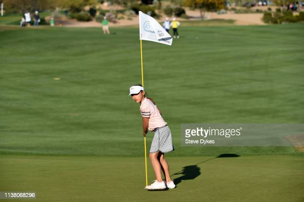 A member of the LPGAUSGA Girls Golf of Phoenix returns the flag stick on the 18th green during the final round of the Bank Of Hope Founders Cup at...
