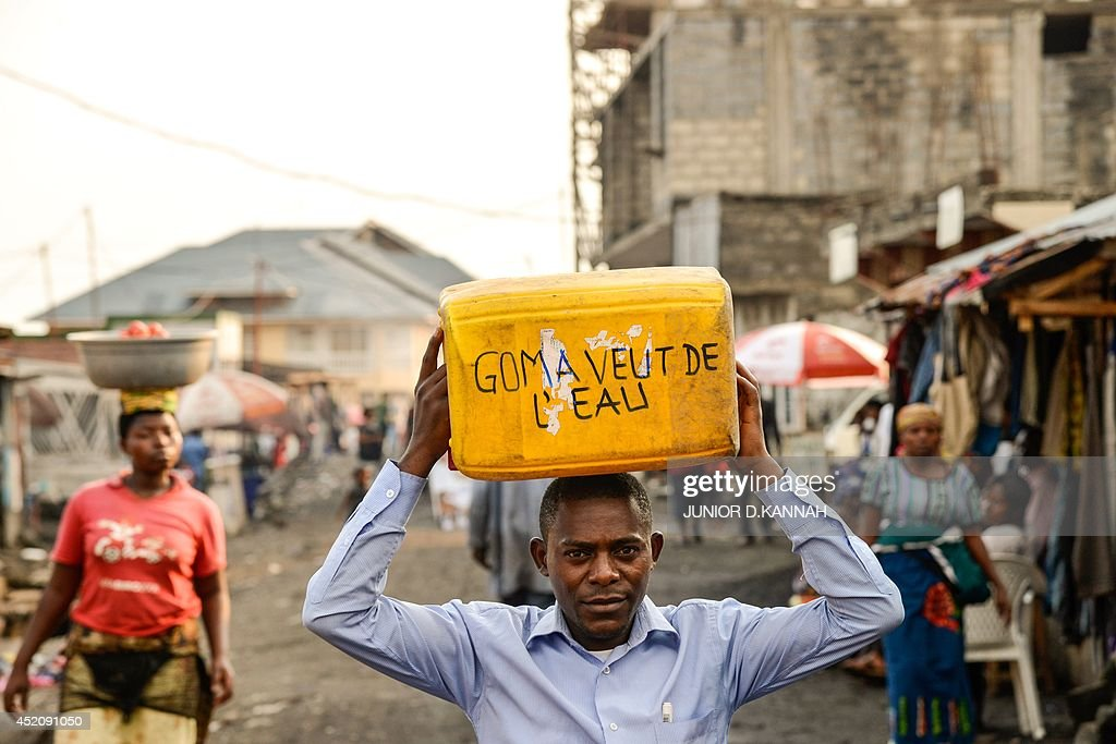 A member of the Lucha association, campaingning for tap water, walks on June 16, 2014 with an empty water container on his head, with the slogan 'Goma wants water,' in the northeastern city of Goma, where most of the one million residents of the city are still waiting to have clean, uncontaminated running tap water in their homes. Goma lies on the edge of one of the largest soft water reservoirs in the world, lake Kivu, where it is rains abundantly, but most people have to go to the lake to fetch water, chlorinate it for drinking or buy it some from sellers, who make about 10 US dollars a day, transporting an average of 120 liters (30 gallons) on bicycles from the lake to the city. Goma, which borders Rwanda, has seen its population explode with refugees from Rwanda, nearby Burundi and internally-displaced Congolese, fleeing the numerous conflicts in the region.
