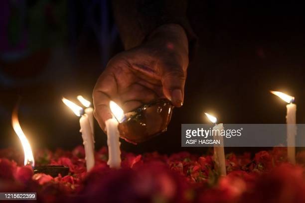 A member of the Majlis WahdateMuslimeen a Pakistani Shiite political organization lights candles in Karachi on May 27 during a vigil for the victims...