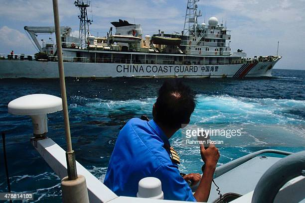 A member of the Malaysian Navy makes a call as their ship approaches a ship belonging to the Chinese Coast Guard during an exchange of communication...