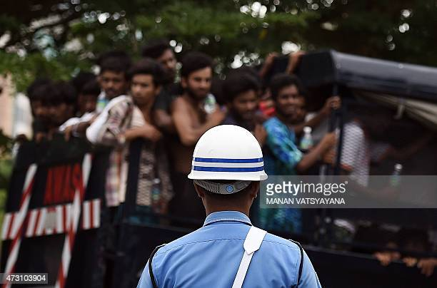A member of the Malaysian Navy stands guard as a truck carrying Bangladeshi and Rohingya migrants from a temporary detention centre arrives at a...