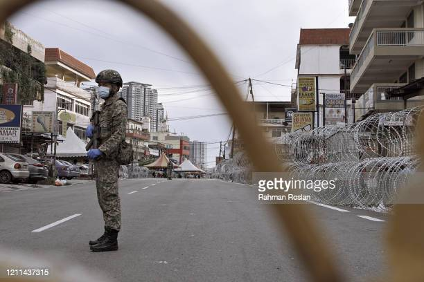 Member of the Malaysian Royal Armed Force guards a street in a neighbourhood that has been put under Enhanced Movement Control Order on May 1, 2020...