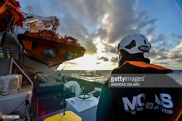 A member of the Maltese NGO MOAS watches the sea aboard the Topaz Responder ship during a navigation to reach the rescue area off the Lybian coasts...