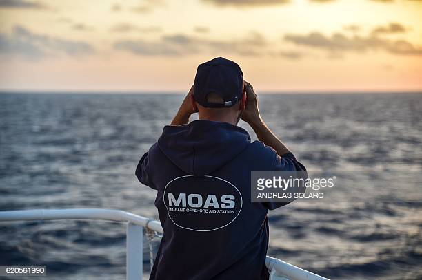 A member of the Maltese NGO MOAS watches the sea with binoculars aboard the Topaz Responder ship during a navigation to reach the rescue area off the...