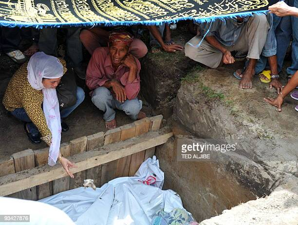 A member of the Mangudadatu clan releases a chick into the mass grave of dead family members during a funeral in Buluan in the southern Philippine...