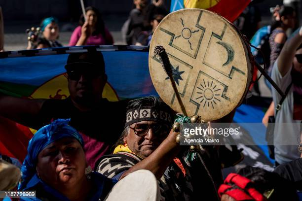 Member of the Mapuche community plays a drum called kultrung as part of a ceremony at Plaza de Armas during a protest against president Sebastian...