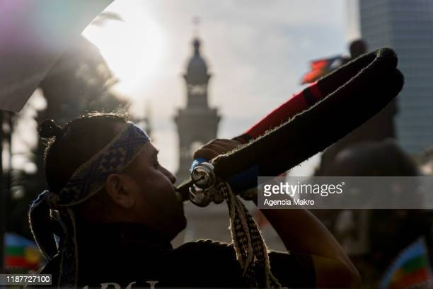 Member of the Mapuche community plays a musical instrument called trutruka while performing a ceremony at Plaza de Armas during a protest against...