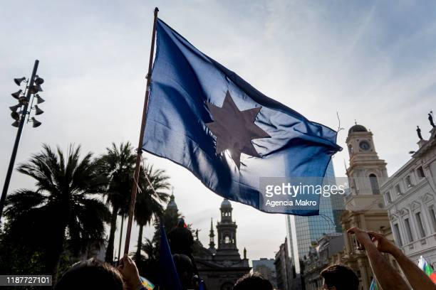 Member of the Mapuche community waves the old Mapuche flag while performing a ceremony at Plaza de Armas during a protest against president Sebastian...