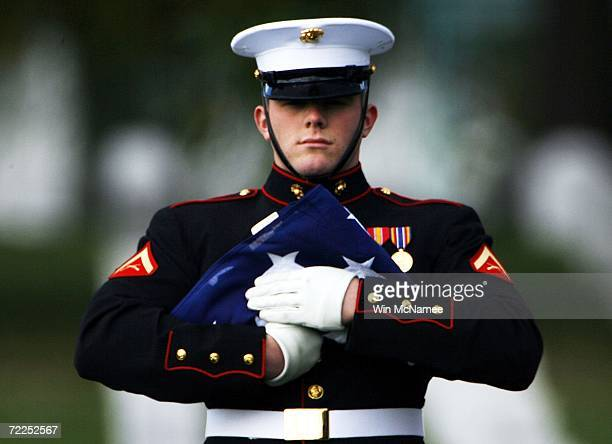 A member of the Marine Corps honor guard holds an American flag during bural services for Sgt Justin Walsh United States Marine Corps at Arlington...