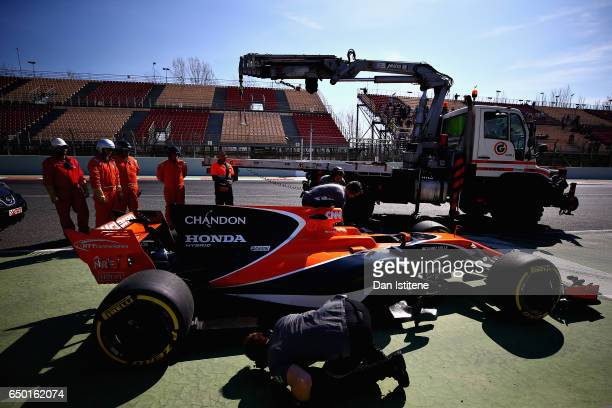 A member of the McLaren team inspects the car of Stoffel Vandoorne of Belgium and McLaren Honda after it stopped on track during day three of Formula...