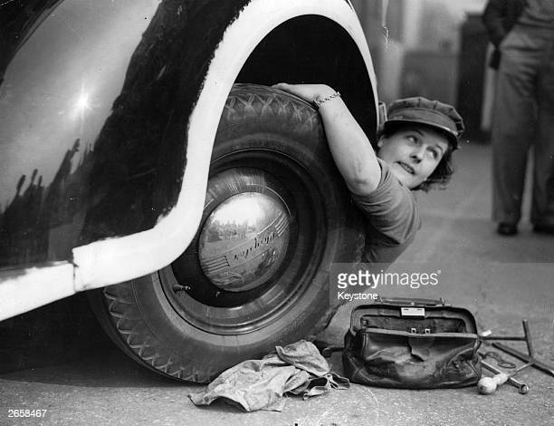 Member of the Mechanised Transport Training Corps changes a wheel at an ARP post in Lambeth, south London.