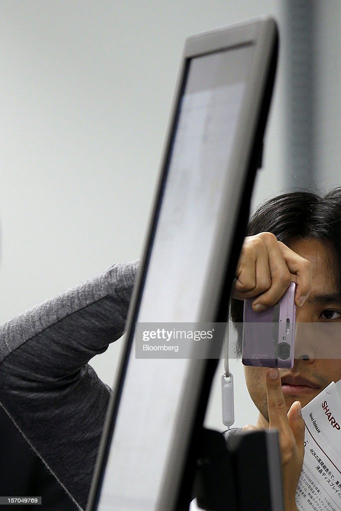 A member of the media examines a Sharp Corp. PN-K321, 32-inch 4K2K liquid crystal display (LCD) IGZO monitor during the unveiling in Tokyo, Japan, on Wednesday, Nov. 28, 2012. Sharp, Japan's largest maker of liquid-crystal displays, has lined up customers for its most advanced panels after saying earlier this year it was struggling to find buyers. Photographer: Kiyoshi Ota/Bloomberg via Getty Images