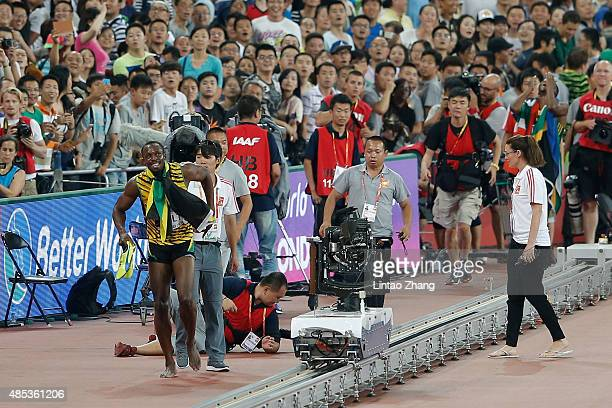 A member of the media falls down in the melee as Usain Bolt of Jamaica celebrates after crossing the finish line to win gold in the Men's 200 metres...
