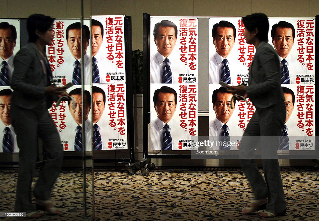 A member of the media is reflected in a mirror as she walks past posters of Naoto Kan, Japan's prime minister and president of the Democratic Party of Japan (DPJ), at the party's election center in Tokyo, Japan, on Sunday, July 11, 2010. Kan's Democratic Party of Japan probably lost control of the upper house of parliament in today's election, its biggest setback since taking power 10 months ago, public broadcaster NHK and Kyodo News projected. Photographer: Haruyoshi Yamaguchi/Bloomberg via Getty Images