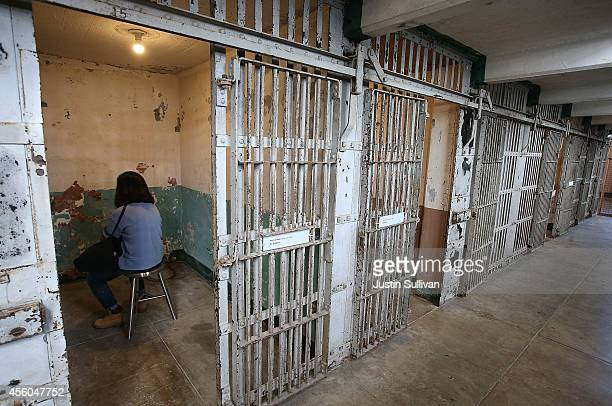 A member of the media listens to audio in a cell that is part of Ai Weiwei's Stay Tuned installation at the @Large Ai Weiwei on Alcatraz on September...