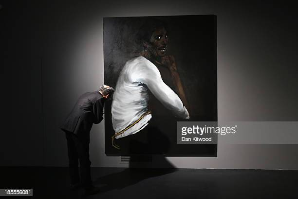 A member of the media looks at a painting by Turner Prize nominated artist Lynette YiadomBoakye in Building 80/81 a former Army base in Ebrington...