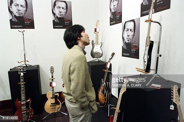 A member of the media looks at some of the 100 guitars used by British guitarist Eric Clapton shown at a media preview 17 June that will be auctioned...