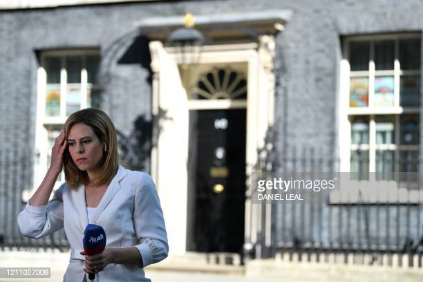 Member of the media prepares to deliver a report outside 10 Downing Street in London, on April 26 as Britain's prime minister Boris Johnson is...