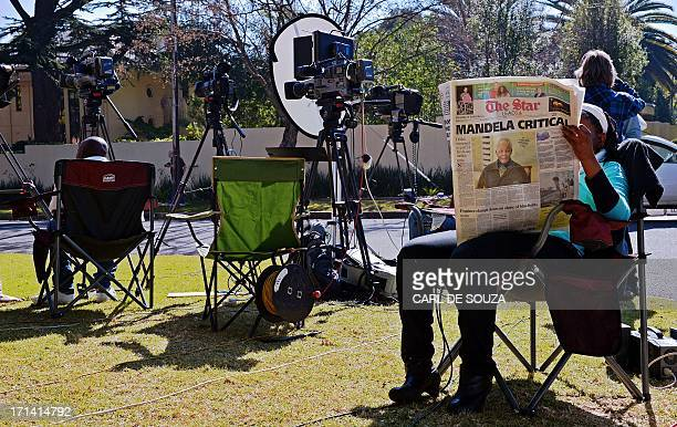 A member of the media reads a newspaper outside the home of former South African President Nelson Mandela in Johannesburg on June 24 2013...