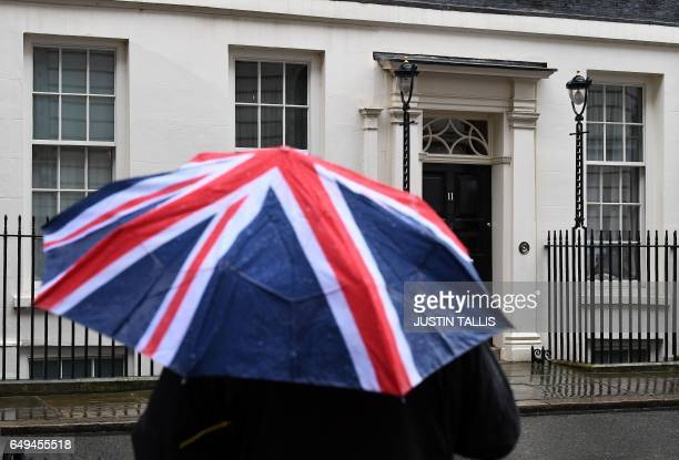 A member of the media shelters from the rain beneath a Union flag themed umbrella outside 11 Downing Street the official residence of British...
