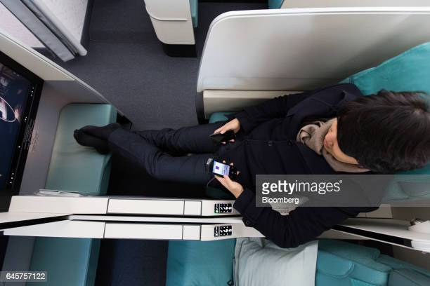 A member of the media sits on a business class seat onboard a Boeing Co 7879 Dreamliner passenger aircraft operated by Korean Air Lines Co during a...