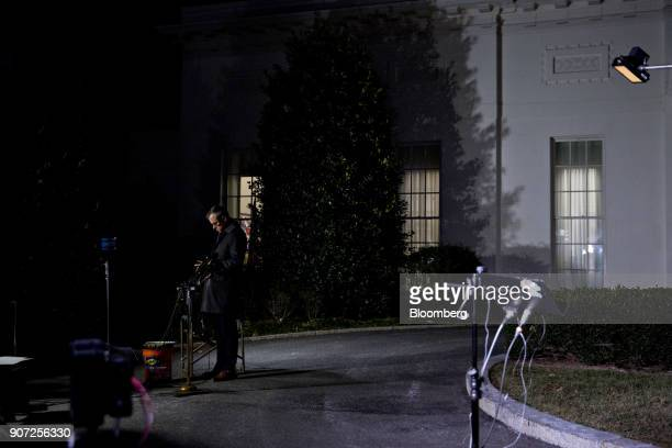 A member of the media stands outside the White House in Washington DC US on Friday Jan 19 2018 Temporary government funding runs out at midnight...