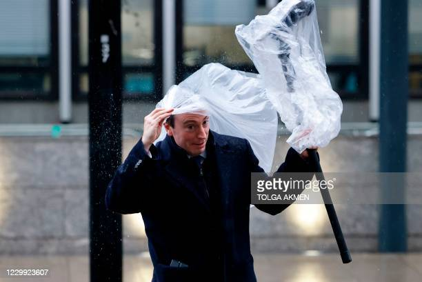 Member of the media struggles to keep his equipment covered in the rain as he waits outside a conference centre where talks continue on a trade deal...