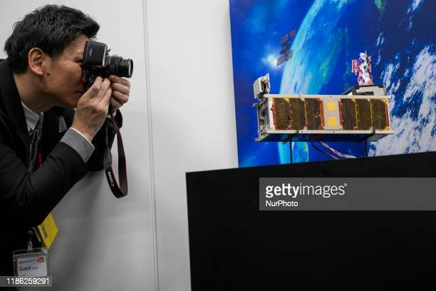 Member of the media take photograph of the miniature satellites payload comprise two of Japans most popular animated characters Mobile Suite Gundam...