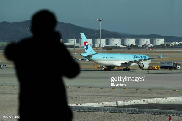 A member of the media takes a photograph of a Korean Air Lines Co aircraft inside the nearly completed terminal 2 during a media preview at Incheon...