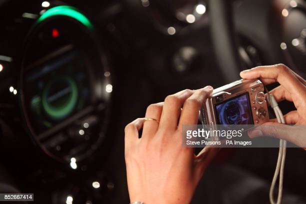 A member of the media takes a photograph of the interior of the new BMW Mini as it is unveiled at their plant in Oxford to coincide with the 107th...