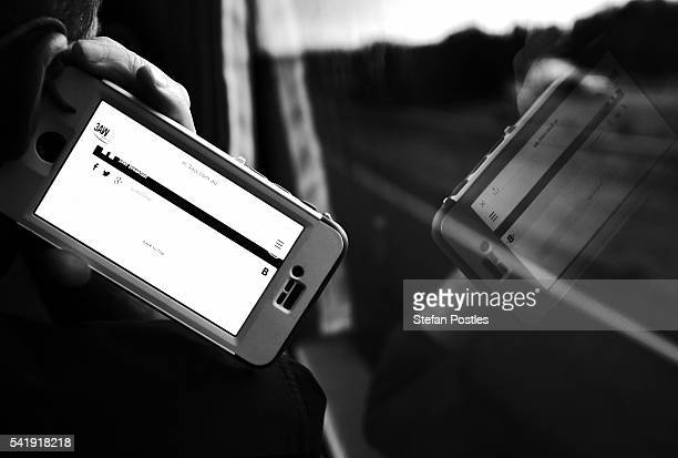 A member of the media traveling with the Prime Minister listens to the news on his phone on June 19 2016 in Sydney Australia