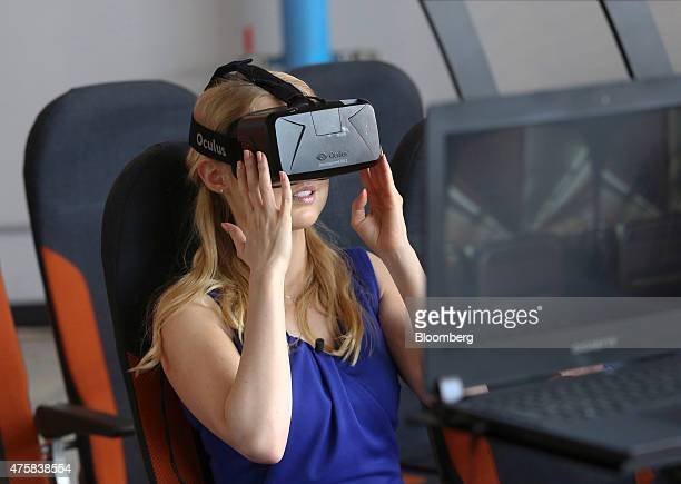 A member of the media tries an Oculus VR Inc virtual reality headset used to train Easyjet cabin crew during a demonstration at the 'Easyjet Plc...