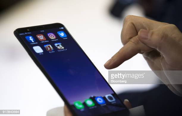 A member of the media tries an Oppo R11s smartphone during a launch event of the smartphone for the Japanese market in Tokyo Japan on Wednesday Jan...