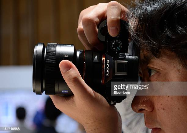 A member of the media tries out Sony Corp's A7 mirrorless digital camera at an unveiling in Tokyo Japan on Wednesday Oct 16 2013 Sony which is...