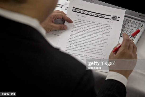 A member of the media views a Federal Reserve press release ahead of a news conference following a Federal Open Market Committee meeting in...