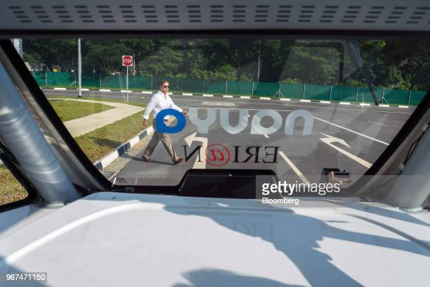 A member of the media walks out in front of a Navya SAS autonomous electric passenger bus to demonstrate the emergency breaking system of the vehicle...