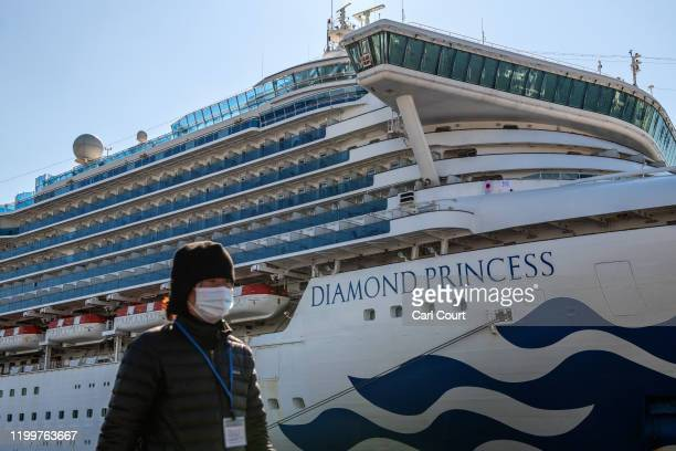 A member of the media wearing a face mask walks past the Diamond Princess cruise ship at Daikoku Pier where it is being resupplied and newly...