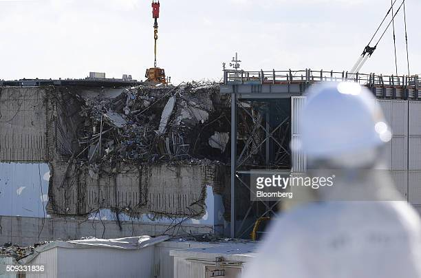 A member of the media wearing a protective suit and a mask looks at the No 3 reactor building at Tokyo Electric Power Co's Fukushima Daiichi nuclear...