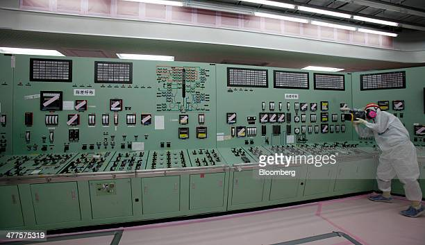 A member of the media wearing a protective suit and mask films inside the central control room for the No 1 and No 2 reactors at Tokyo Electric Power...