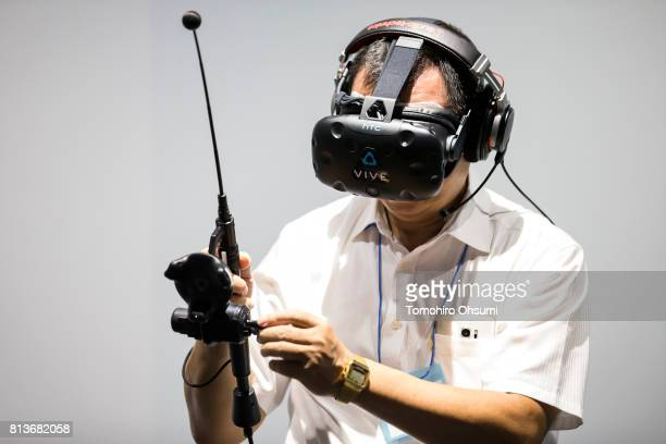 A member of the media wearing an HTC Corp Vive virtual reality headset tries the Gijiesta VR attraction at the VR Zone Shinjuku theme park operated...